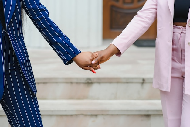 Een liefdevol lesbisch koppel hand in hand. handen samen twee afrikaanse lesbische meisjes