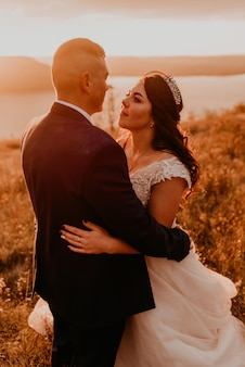 Een liefdevol paar bruiloft jonggehuwden in witte jurk en pak lopen knuffel kussen werveling op hoog gras in zomer veld op berg boven de rivier