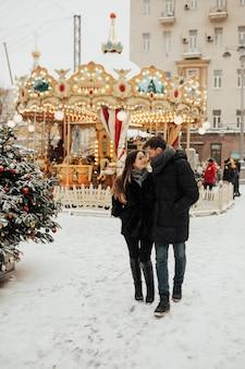 Een liefdevol paar dat in de sneeuwtijd dichtbij de carrousel loopt