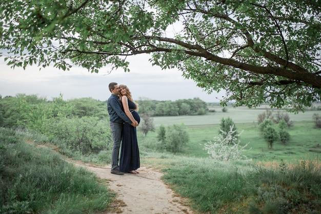 Een liefdevol stel loopt in het veld, het meisje is zwanger. loop in de frisse lucht. liefde en zorg.