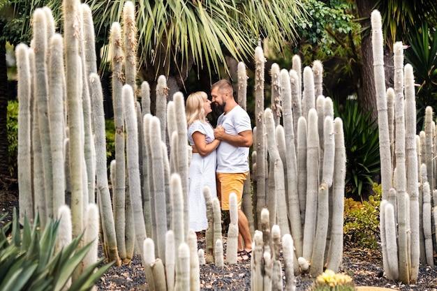 Een liefdevol stel omhelst elkaar tegen de achtergrond van enorme cactussen op het eiland tenerife