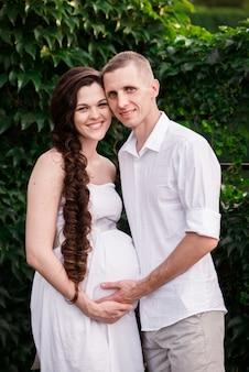Een liefdevol zwanger paar knuffels in een zomer park en glimlacht