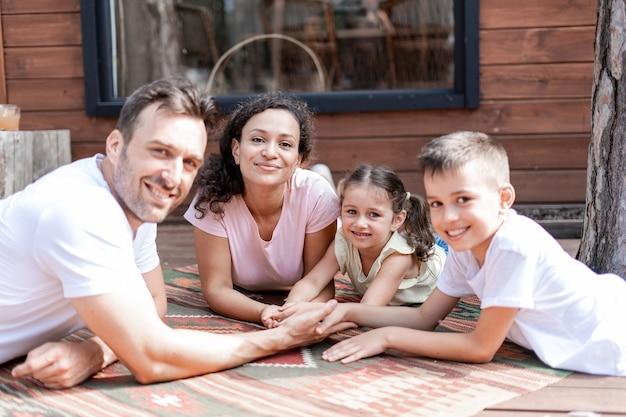 Een liefdevolle, vriendelijke en zorgzame familie ligt bij elkaar in de buurt van een houten huis en houdt elkaars hand vast. moeder, vader, dochter en zoon brengen samen tijd door tijdens de zomervakantie.