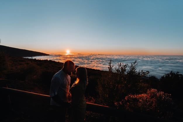 Een liefhebbende man houdt de hand van het meisje vast bij zonsondergang, op de achtergrond van de zee, portret van knappe pasgetrouwden. foto, concept.