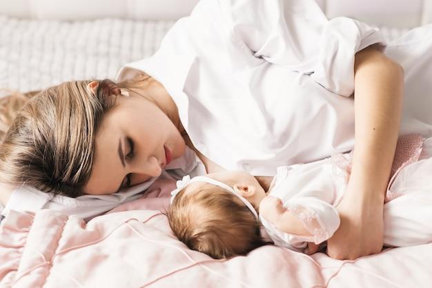 Een liefhebbende moeder draagt haar pasgeboren baby thuis. portret van een gelukkige moeder met een slapende baby in haar armen. moeder knuffelt haar dochtertje van 4 maanden