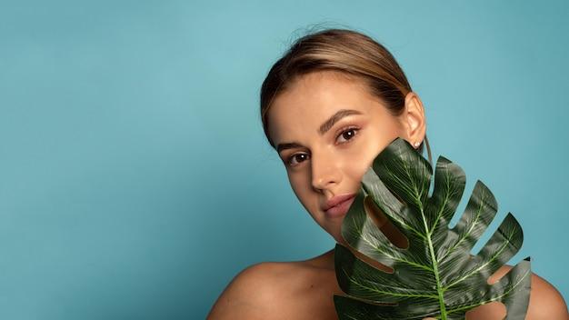 Een lieftallig vrouwelijk model bedekt een deel van haar gezicht met een tropisch palmblad. huidverzorging, hydratatie. cosmetica met natuurlijke ingrediënten. webbanner.