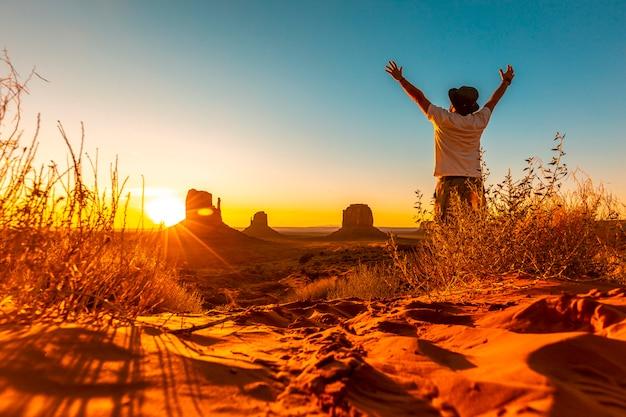 Een lifestyle-man met een hoed en open armen bij zonsopgang in monument valley, utah