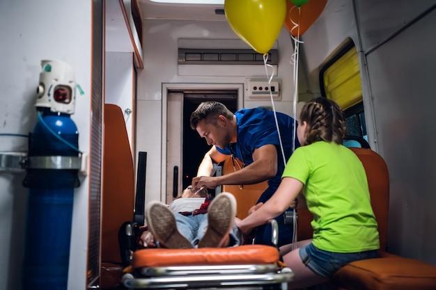 Een lijkschouwer in een uniform die een zuurstofmasker aanbrengt op een bewusteloze vrouw, liggend op een brancard in een ambulance-auto