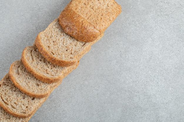 Een lijn van sneetjes bruin brood op een grijze achtergrond.