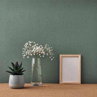 Een lijst, een vaas met witte bloemen en een kamerplant in een pot staan op een kurkvloer