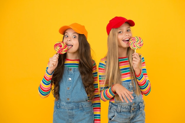 Een lik hebben. kleine meisjes genieten van heerlijke smaak van lolly's op gele achtergrond. kleine kinderen die snoepjes likken met klassieke fruitsmaak. het smaakt zo goed. zoete smaak van de kindertijd.