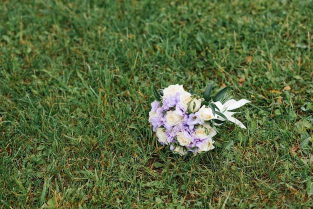 Een lila en beige bruiloft boeket ligt op het groene gras. ruimte kopiëren