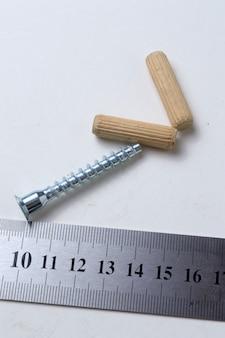 Een liniaal, een meubelschroef en een houten deuvel liggen. detailopname.