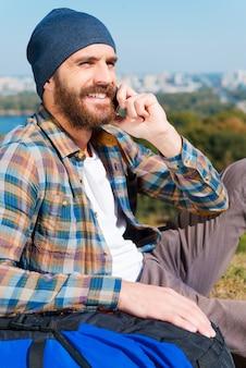 Een link vinden voor een oproep. knappe jonge man zit in de buurt van rugzak en kijkt weg met een glimlach terwijl hij telefoneert