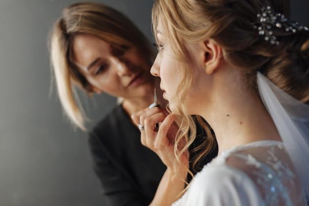 Een lippenpotlood aanbrengen. bruiloft make-up. visagist schildert lippenstiftmeisje. make-up artiest in proces in. mooi vrouwengezicht. met avond make-up. hand van make-up meester.