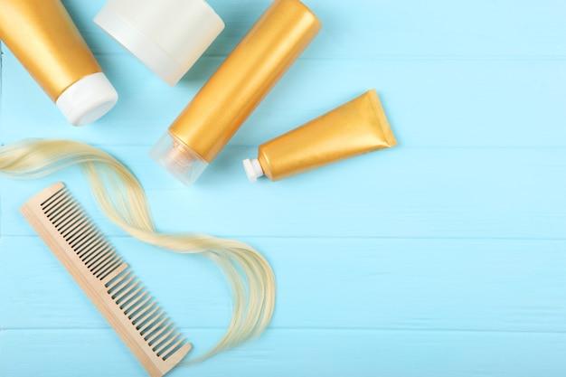 Een lok blonde haarverzorgingsproducten en een kam op een gekleurde achtergrond