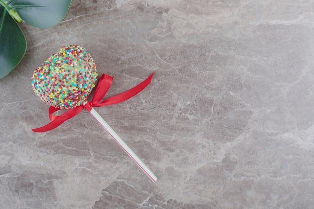 Een lolly en een decoratief blad op marmer Gratis Foto