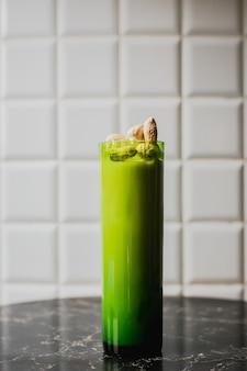 Een longdrinkcocktail in een groen longdrinkglas gegarneerd met pinda's