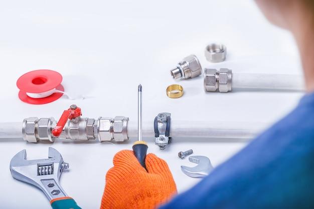 Een loodgieter repareert een waterlek op een waterleiding
