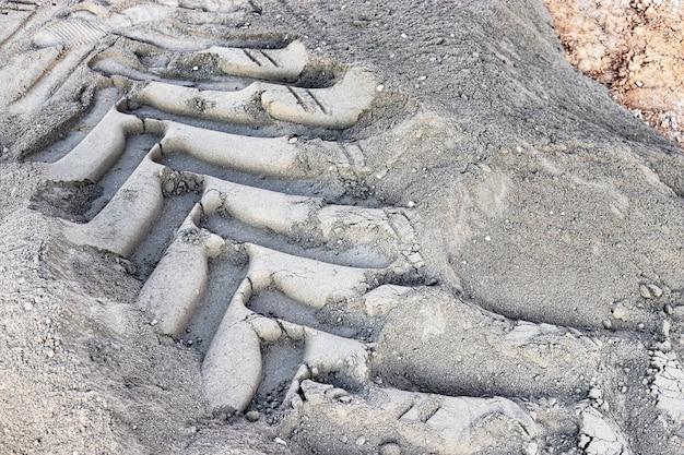 Een loopvlakteken van een wiel van een bouwvoertuig op de grond. opdruk van zware machines. wielvorm van gedroogde modder.