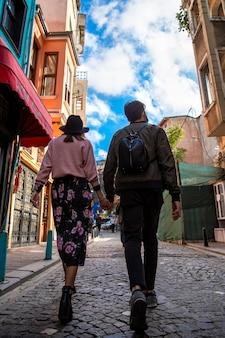 Een lopend stel dat elkaar vasthoudt lopend op een voetgangersstraat, groothoekopname, rijen gebouwen in istanboel, turkije