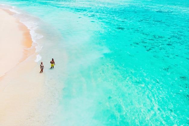 Een luchtfoto van een paar staande op een tropisch strand met uitzicht op brekende golven op een tropisch gouden zandstrand.