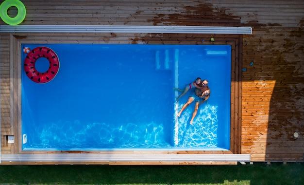 Een luchtfoto van vader met kleine kinderen die buiten in het zwembad zitten.