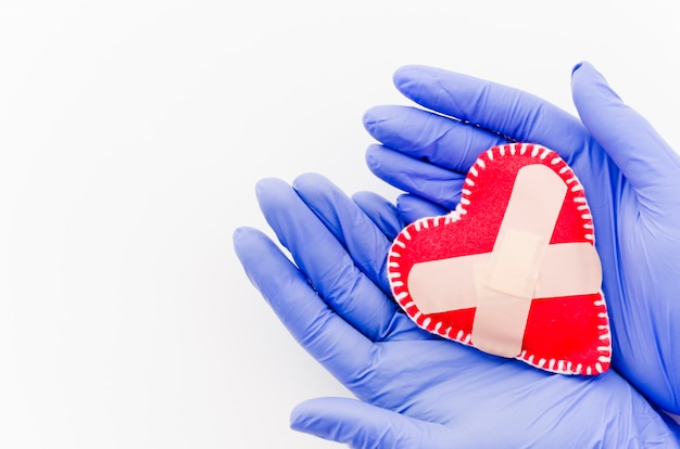 Een luchtmening van de hand van de arts met chirurgische handschoenen die rood hart met verbanden houden die op witte achtergrond worden geïsoleerd