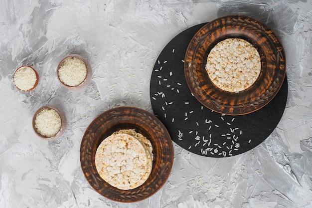 Een luchtmening van de kommen van de rijstkorrel met stapel van gepuft rijst koeken op houten plaat