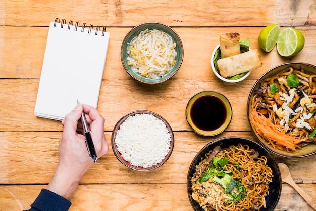 Een luchtmening van een persoon die op pen met spiraalvormige blocnote met thais traditioneel voedsel schrijven