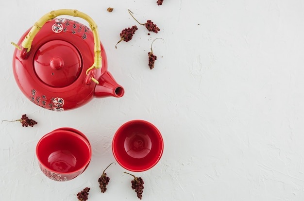 Een luchtmening van rode traditionele die theekop en theepot met kruiden op witte achtergrond wordt geïsoleerd