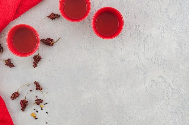 Een luchtmening van rode traditionele theekop met kruiden op grijze geweven achtergrond