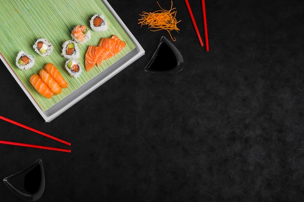Een luchtmening van sushi rolt met geraspte wortel en rode eetstokjes tegen zwarte achtergrond