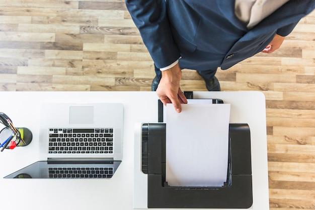Een luchtmening van zakenman die document van printer in het bureau nemen