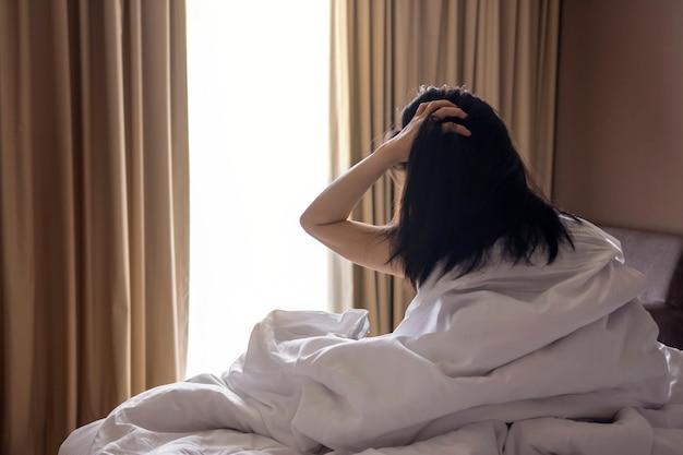 Een luie vrouw met rommelig haar zittend op wit bed
