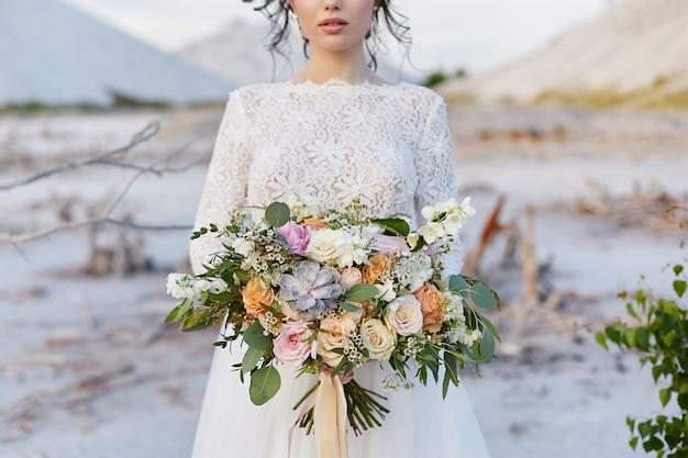 Een luxe boeket exotische bloemen in de hand van een jonge vrouw in een kanten jurk