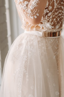 Een luxe bruid in een trouwjurk in de ochtend in haar interieur.