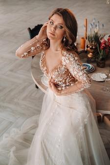 Een luxe bruid in een trouwjurk 's ochtends in haar interieur.