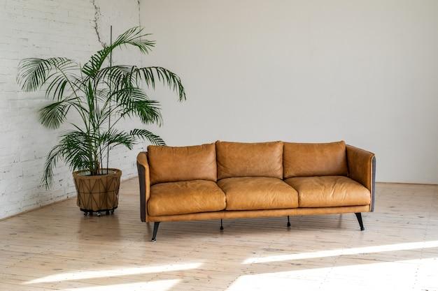 Een luxe grote lichte woonkamer met een grote groene potplant in industriële stijl met een bruin leren bank en een baksteen-witte muur.