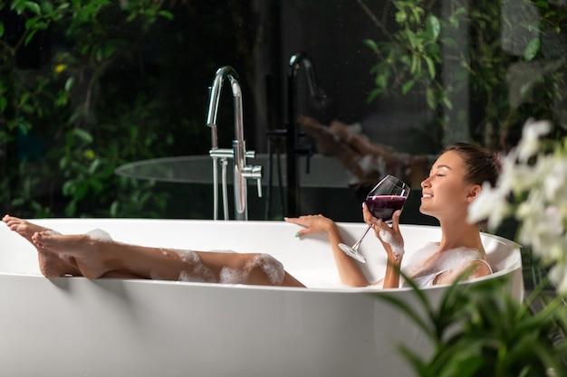 Een luxueus meisje ontspant in een schuimbad met een glas wijn. spa en ontspanning
