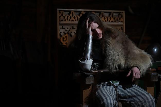 Een machtige held met lang haar in maliënkolderpantser in een oude zaal. middeleeuwse krijger in de ridderkamers.