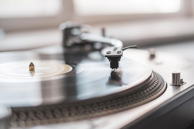 Een macro dichte omhooggaande platenspelernaald die de vinylschijf, ouderwetse retro muziekspeler speelt