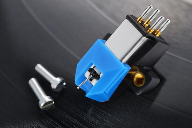 Een magnetische phono-cartridge op vinylplaten. macrofoto.