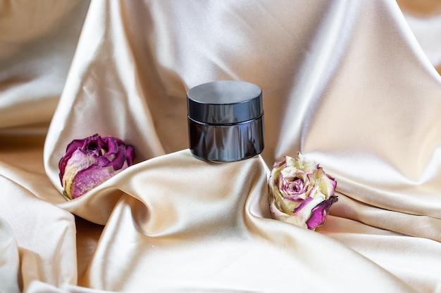 Een make-upcontainer van donker glas ligt op plooien van zijdesatijn, omgeven door gedroogde rozenbloemen