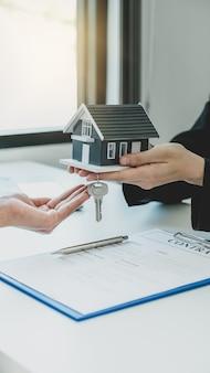 Een makelaar geeft een woningmodel aan de kopende vrouw.