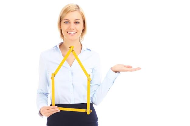 Een makelaar in onroerend goed die gele maatregel toont en over witte achtergrond wijst