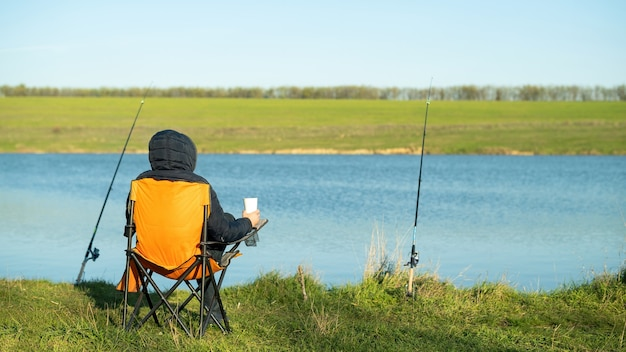 Een man aan het vissen, zittend in een stoel en met een beker, twee hengels op standaards