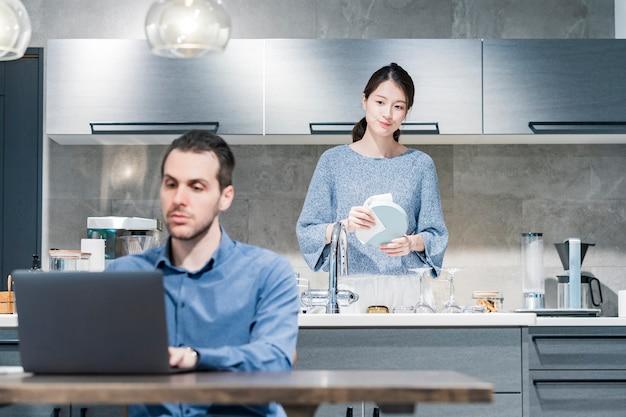 Een man aan het werk aan een eettafel en een vrouw afwassen in de keuken