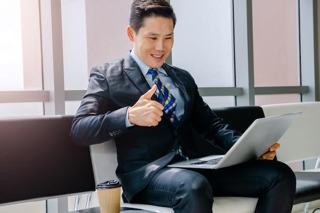 Een man aan het werk met een notebook koffie drinken zittend in een stoel