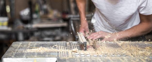 Een man aan het werk met houtproduct op de machine, close-up
